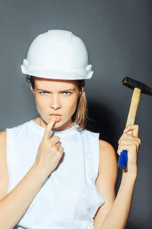 workwoman: Young girl professional engineer with pretty thoughtful face in white building helmet with hard hammer instrument holding finger near mouth on grey background studio