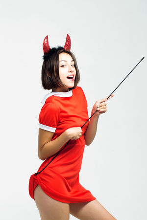 young sexy halloween woman or girl with pretty smiling face in red dress and devil horns or antlers holiday costume holds stick isolated on white background Stock Photo