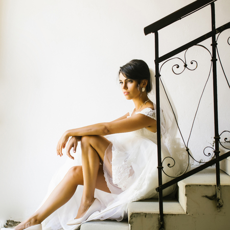 long sexy legs: Beautiful bride woman with long sexy legs in white wedding dress and veil sits on staircase Stock Photo