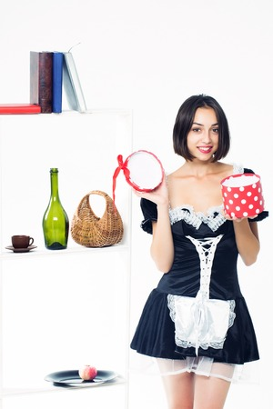 sexy maid: Young girl with beautiful smiling face in black sexy maid uniform holding open red present box posing near shelves with kitchenware isolated on white background Stock Photo