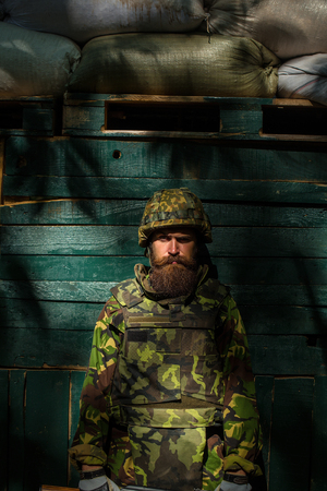 Handsome bearded man in camouflage. Portrait of bearded soldier in front of the green wooden background Stock fotó