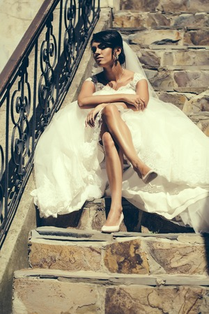 long sexy legs: Beautiful bride woman with long sexy legs in white wedding dress and veil sits outdoors on stone steps