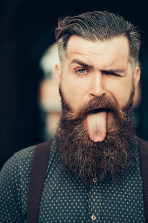grimace: young handsome bearded man portrait with long beard and moustache has stylish hairdo in shirt outdoor showing tongue on grimace face Stock Photo