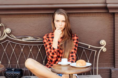 Mädchen ziemlich schlank Modell in rot karierten Hemd und Shorts leckt Finger auf Vintage-Trainer in Kaffee Café Standard-Bild - 63536064