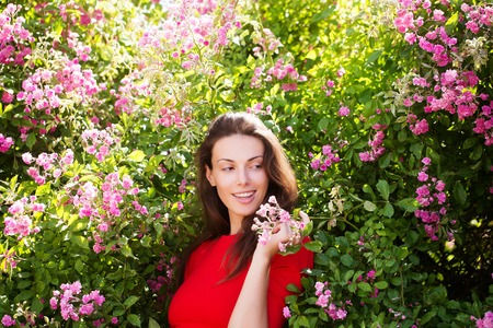 Pretty girl or woman young female model with brunette hair in red dress poses among blossoming flowers and green leaves on summer sunny day