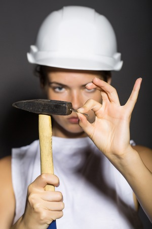 workwoman: Young girl professional repairer in white building helmet holding hard hammer instrument in hand and small nail in other on gray background studio Stock Photo