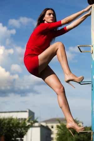 young fashionable woman or girl with long brunette hair and pretty face in stylish red dress on slim body and shoes on high heels climbing on house stairs on blue sky background outdoor