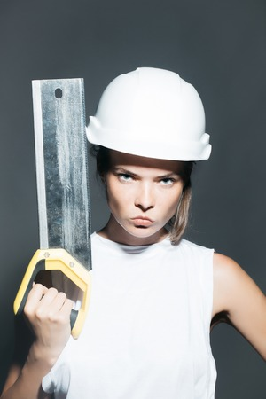 repairer: Young girl workwoman repairer with pretty serious strict face in white building helmet holding professional saw instrument in hand studio on gray background