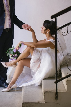 elegant staircase: Elegant groom man holds hand of beautiful bride woman with sexy legs in white wedding dress and veil with bouquet sitting on staircase