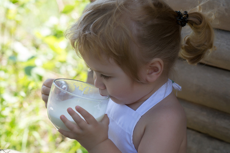pinafore: Cute little boy with blond hair ponytail in white pinafore drinks milk on summer day on wooden background Stock Photo