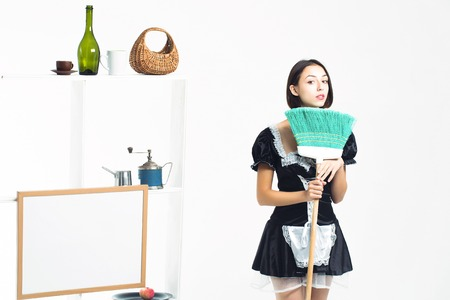 sexy maid: Young girl brunette with pretty face in sexy black maid costume posing with sweep green broom on background of shelves with cookware isolated Stock Photo