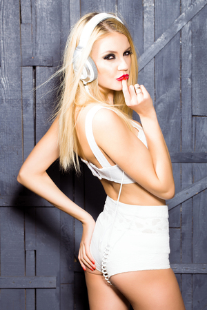 young woman or girl dj with blonde hair and red lips on pretty sexy face in white bra with shorts and musical stereo headphones or headset in studio on wooden background