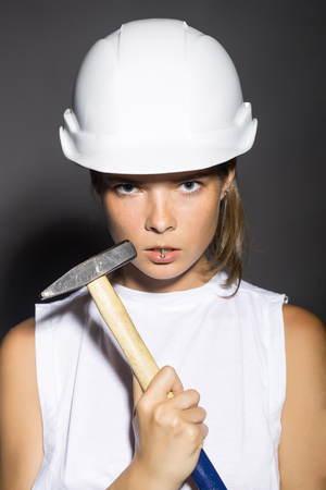 repairer: Young woman professional repairer workwoman in white building helmet holding hard hammer instrument near pretty face studio on grey background