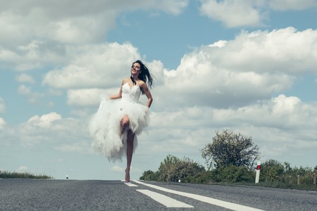 young wedding happy sexy girl or woman with brunette hair and pretty face in white bride dress running on road way on cloudy blue sky background