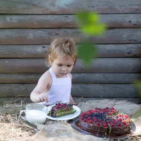 Cute little boy in white pinafore eats fruit cake and cup of milk at table outdoors on wooden background Banco de Imagens