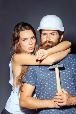 Young woman with pretty face hugging man repairman with bearded serious face in white building helmet holding hard hammer instrument studio on grey background