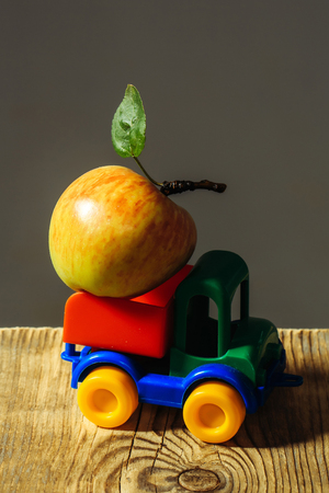 Plastic colorful toy truck with one fresh apple with leaf on peduncle on wooden table on grey background