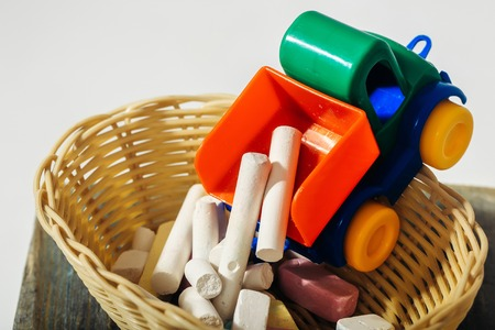 white chalks: Plastic toy car unloads colorful chalks to small basket on wooden board on white background Stock Photo
