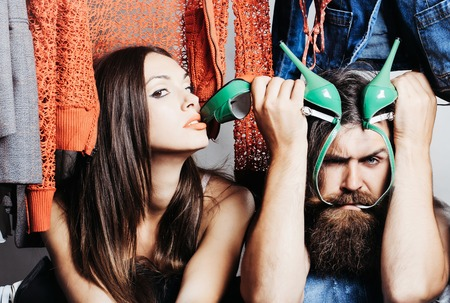 Fashion couple denuded tired of brunette girl with long hair and bearded man with green high heels shoes among clothes to wear near rack in closet Stock Photo