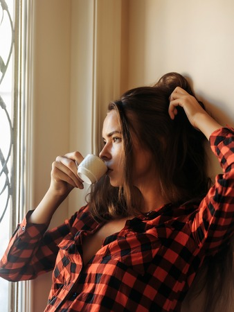 unbutton: Sexy pretty girl with long brunette hair in unbutton in red checkered shirt drinks coffee and looks at window
