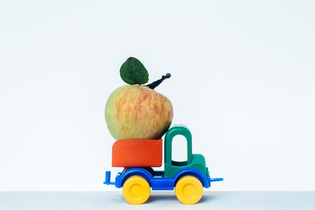 Plastic colorful toy car with one ripe apple with leaf on peduncle on white studio background