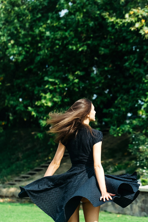 sexy girl dance: Attractive sexy young girl with long dark hair and spinning navy dress looks away