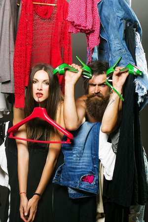denuded: Fashion couple denuded tired of brunette girl with red hangers and bearded man with green high heels shoes among clothes to wear near rack in closet