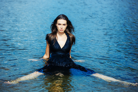 spreaded: Sexy young girl in navy dress with long dark hair sits in water with spreaded legs