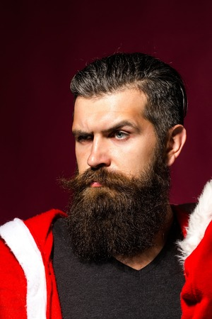 brows: Handsome man hipster male with long beard and moustache in santa coat bends brows on purple background