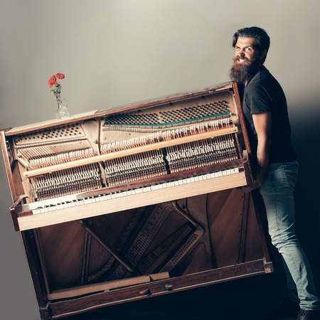 handsome bearded strong man with stylish hair mustache and beard trying to move old wooden or wood open piano with keyboard and glass vase with red rose flowers on grey background, copy space