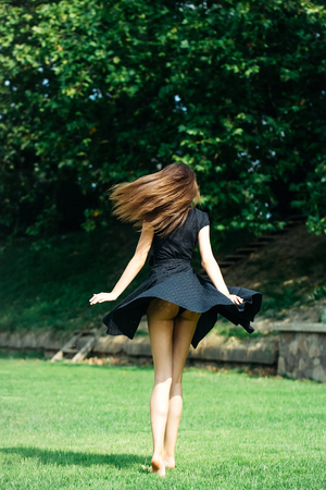 sexy girl dance: Attractive sexy young girl with long dark hair and navy blowing up dress jumps on the lawn Stock Photo