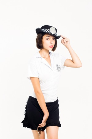 wristbands: Young girl brunette with pretty sexy face posing on white background in policewoman costume t shirt black skirt and cap holding iron wristbands in hand isolated