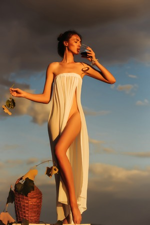 denuded: Pretty girl in white sexy dress denuded gorgeous body drinks red wine from glass with wicker bottle vine grapes over dramatic sky