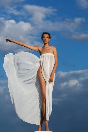 denuded: Pretty young girl or woman with slim body in white sexy dress denuded posing on nature over sunny blue sky background