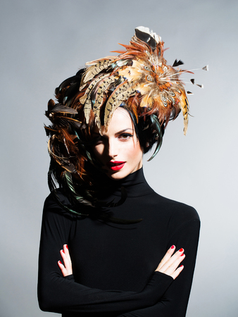 young sexy woman or girl with red lips on pretty face in beautiful feather hat brown color as halloween or carnival holiday costume on grey background