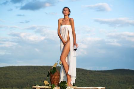 Recht junges Mädchen oder Frau im weißen sexy Kleid entblößte mit Rotwein in der Glasweidenflaschenrebe und -trauben auf Natur über blauem Himmel
