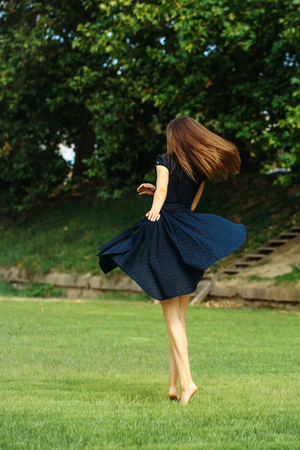 sexy girl dance: Attractive girl with dark long hair and black dress spinning on the lawn Stock Photo