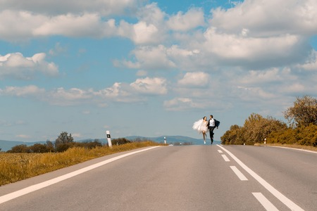 married couples: Beautiful bride and handsome groom elegant fashion married couple in wedding dress and suit run along road and hold hands on blue sky Stock Photo