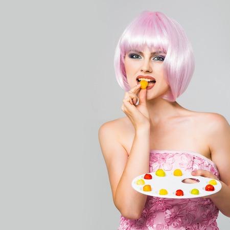 paletas de caramelo: muchacha atractiva del encanto o una mujer con maquillaje de moda en cara bonita y el peinado corto y peluca rosa en traje de comer dulces mermelada de colores en la paleta de colores en el estudio sobre fondo gris, espacio de la copia