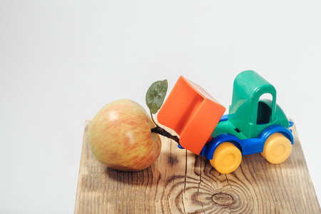 Small colorful toy truck unloads fresh apple with leaf on peduncle on wooden board on white background
