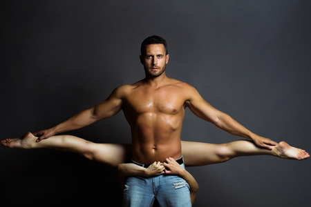 sexy girl dance: young sexy couple of handsome muscular man in jeans with bare torso holds pretty flexible woman or girl dancing contemporary or modern gymnastic dance in studio on grey background, copy space Stock Photo