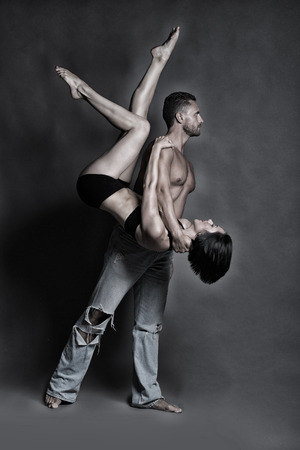 sexy girl dance: young sexy couple of handsome muscular man in jeans with bare torso holds pretty flexible woman or girl dancing contemporary or modern gymnastic dance in studio on grey background Stock Photo
