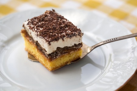 Sponge cake with cream and chocolate on slice on white plate on yellow checkered tablecloth Stock Photo