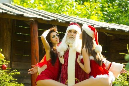 half nude: Santa Claus hugs sexi half nude girls in christmas costumes outside