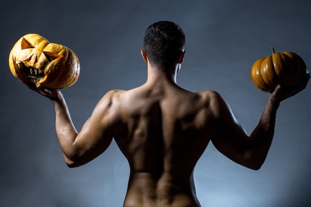 Young handsome man with muscular body and bare back posing in studio holding yellow halloween pumpkins on grey background Stock Photo