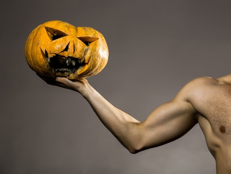 muscular male hand holding yellow halloween pumpkin with scary face in studio on grey background