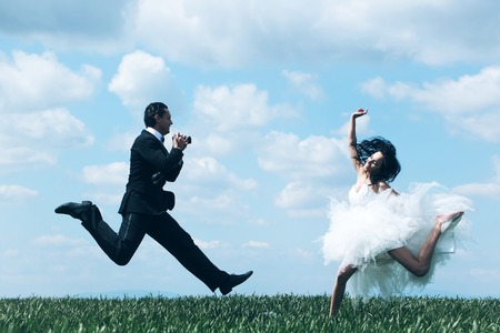 fashion photos: Happy bride and handsome groom elegant fashion married couple in wedding dress suit jump and take photos on beautiful field on blue sky