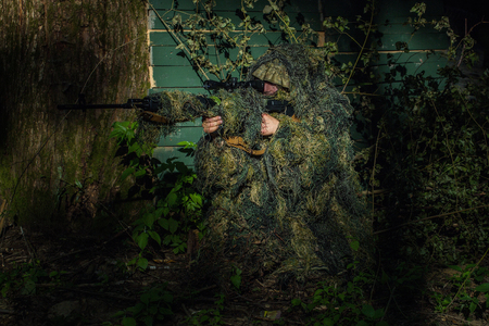 aggressiveness: Sniper soldier in ghillie suit camo and mask sitting with rifle aiming target near tree and green branches background Stock Photo