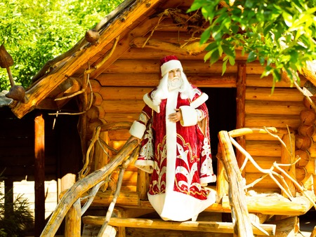 log house: Man in red santa costume standing near entrance to log house with beautiful wooden stairs outdoor Stock Photo