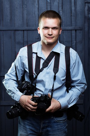 young handsome man photographer with smiling face in shirt with many photo cameras equipment of journalist or reporter professional in studio on wooden background